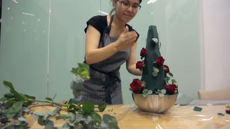 kwiaciarnia : Asian florist prepares roses for a bouquet of green sponge. Wideo