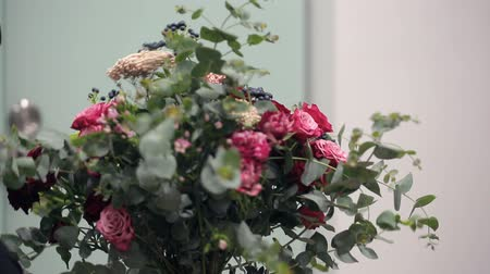 floral composition : Florist Asian collects a bunch of red, pink and white roses and berries. Stock Footage