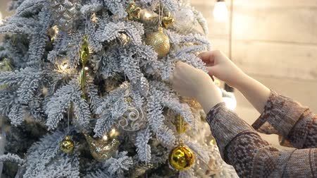 вешать : Somebody tie gold ribbon from organza as decoration to Christmas tree. Стоковые видеозаписи