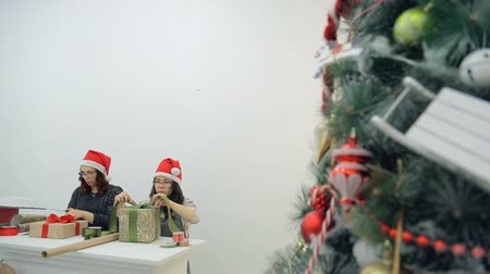вешать : Two women prepare new year presents for Christmas holidays in office.