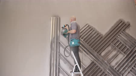 ar : A man stands on a ladder and paint spray detail design construction.