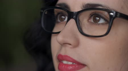 ношение : Close-up portrait of a beautiful woman in glasses who utters words. Стоковые видеозаписи