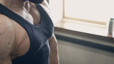 straining : Male athlete doing biceps dumbbell curls in gym indoors. Standing directly holding his elbows close to body and straining muscles of abdominal press he with exhalation raises dumbbells up to level of shoulders and slowly returns to starting position. Youn Stock Footage