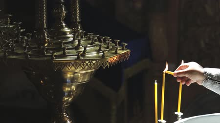 clergyman : clergyman lights candles and puts on candlestick in church indoors Catholic temple. He gently lit three yellow wax candles from burning one which he holds in hand and places it on metal multi-level candelabrum