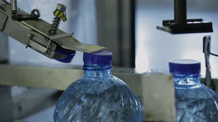 ivászat : Process of closing plastic bottles with water in company. Blue bottles with clean drinking aqua move along conveyor belt while it is closed by lids with using of metal equipment in production premises of modern enterprise.