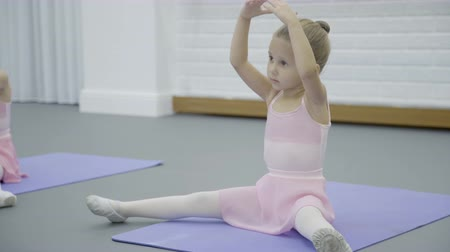 balerína : The girl does half split body bent during the ballet class in beautiful studio. The little dancer in pink dress sits on the lavender mat and inclines up and down with raised hands during the exersice. The room is bright with brick white walls.
