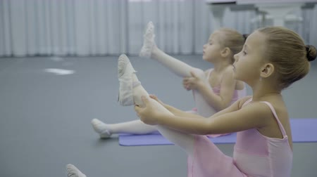 balerína : Girls ballerina sit on mat and pull up one leg for stretching muscles. Little children in dance studio perform exercises to develop flexibility. Dostupné videozáznamy