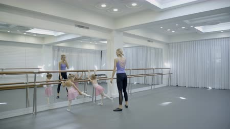beautifully : The trainer teaches two girls how to turn around beautifully while ballet class. The teacher showes how to stand on the tips of the toes straight, raises her arms upward and twist right. The little dancers copy her motions in front of the big mirrow. Stock Footage