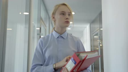 только один человек : The portrait of blonde female secretary who is looking for her boss in the office. The manager in blue shirt is holdin the red folder with documents in her hands and turning her head while going through the corridor with glass room walls.