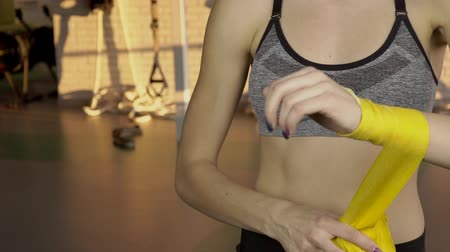 lasting : Young woman is bandaging arm with bandage, standing in sports club. Lady wraps wrist with yellow fabric dressing before training. Female athlete dressed in short top, emphasizing abdominal press with earring in navel, is preparing to intensive workout, us