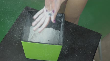 fricção : Female hands rub on skin white sport magnesia from square container. Woman athlete uses powder to increase friction between fingers and fitness equipment.