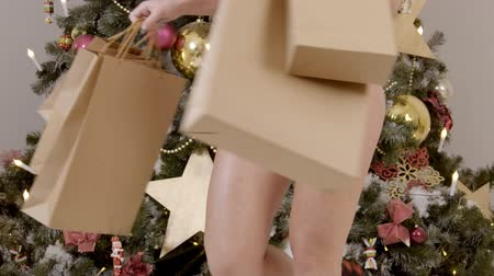 computação gráfica : Sexy model is moving with gifts near New Year tree in room. Beautiful lady with bare buttocks, posing by Christmas fir in studio. Attractive woman in red costume with bare legs and butts, postures sensually, holding packages with presents in hands near gr