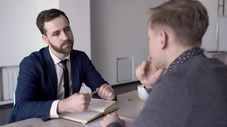 two people talking : Man with beard listens to client in office at table to job in business. Serious businessman makes an interview with a male person and holds a pen over his notebook.