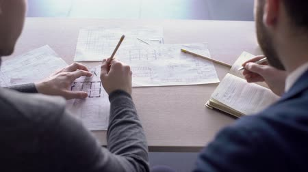 appraisal : Two male architects are working together in the office. Men are sitting at the wooden table with papers on. Professional in grey jumper is correcting a blueprint using pencil and ruler and his colleague in suit is taking notes in his notebook.