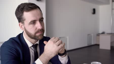 hukuk : Portrait of businessman who is listening to his partner offer on business negotiations. Handsome male professional with beard and beautiful blue eyes is wering suit and tie and shaking his head agreeing with his colleague. Stok Video