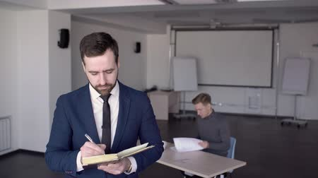suite : In office is a portrait of a business man who makes notes in the diary. Male entrepreneur in suit with beard at beginning of working day makes up a plan and a schedule for day in the business center.
