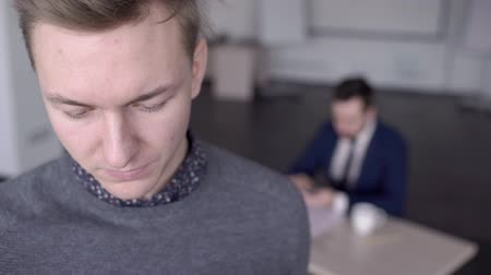 prodavač : Young blond man is standing in the office and reading report. Male professional has a beautiful face with blue eyes and blond hair, and wears grey jumper and shirt for his work. His colleague is sitting at the table behing him and working on the project. Dostupné videozáznamy
