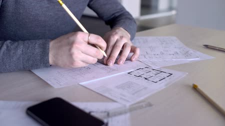 appraisal : Close up of young male arcitect, who is working on the building project in his office. Man is holding ruler and pencil by his hands with golden ring on the finger and drawing a roof of the house on the paper.