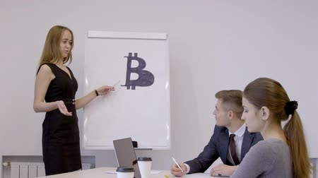 currency trading : Female designer is presenting a logo for bitcoin in the office with her colleagues. Lady is wearing black dress and is standing near whiteboard. Businessman in blue suit and lady in grey blouse are sitting at the wooden table with brand new laptop, papers