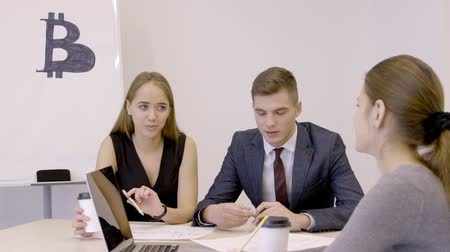 currency trading : Three young traiders are discussing bitcoin investments in start-up office. Businessman and his female collagues are sitting in boardroom at the table with laptop, paper coffee cup and reports on while analyzing digital currency market. slow motion video,