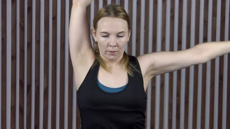 puxar : Adult woman connects hands behind back for development of flexibility. Close-up on background of a striped wall female athlete in a black T-shirt pulls a muscle that would join hands behind spine.