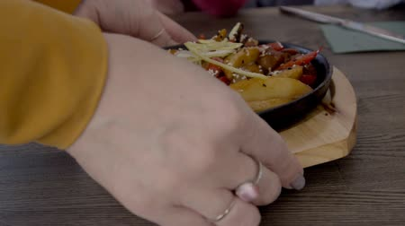 being cut up : Close up of delicious asian dish is being placed to the wooden table by waitress in the restaurant, slow motion. Female stuff is placing black pan with meat and vegetables to the desk by her hands with rings on fingers. Stock Footage