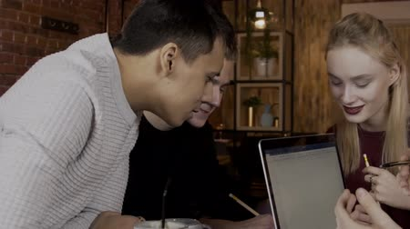 working together : Four colleagues are working on project together in moden cafe with cozy interior. Blond woman and three men in black and white jumpers are sitting at the table and discussing their project, using pencils and brand-new laptop. slow motion video Stock Footage