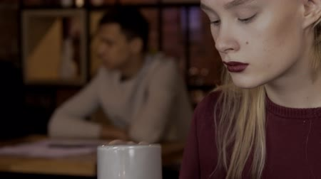 посетитель : Close-up portrait of a beautiful blonde woman who drinks tea in a cafe. Young woman with make-up in burgundy color calmly makes a hot drink and seriously thinks. slow motion video