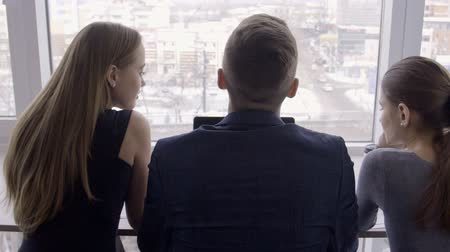 corporate affairs : Three people are talking and looking out window in modern office. Young colleagues speaking while watching of cityscape from window indoors. Two women and man communicate with positive smiles during break from working affairs, admiring beautiful winter vi Stock Footage