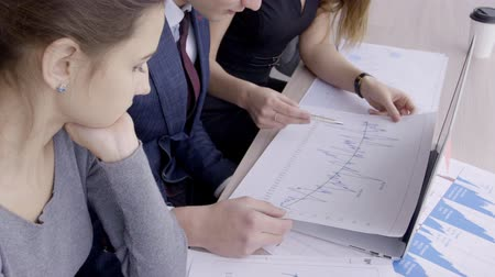 оттенки : Young professionals are discussing blueprint sitting at table in leading company. Business people working on project and talking in modern office. Three employee examine and analyze diagrams depicted on sheets, pointing to nuances with pens. On desk there
