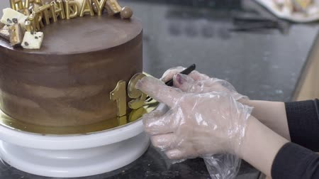 gênero alimentício : Confectioner in gloves makes a cake to 19th anniversary of birthday. Close-up on order in confectionery hand make a dessert with letters of happy birthday, date and candy. slowmotion slow motion
