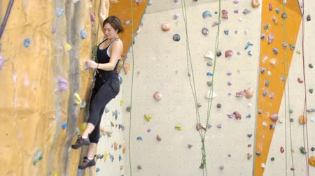 markolat : On climbing woman is hooked on wall in gym during exercise. With an effort female sports person overcomes artificial obstacles during sports practice for courage and endurance.