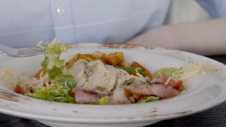císař : Close up of salad, which is being eaten by young lady in restaurant, slow motion. Woman in blue shirt is using steel fork to pick up the pieces of chicken, bacon, chees and potatoes, which are mixed in white plate on wooden table. Dostupné videozáznamy