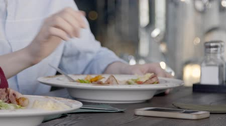 císař : Close up of two people, who are eating salad in the restaurant, slow motion. White plates with delicious dish are standing on wooden table and people are using steel forks. Woman in blue shirt is taling brand-new smartphone from the desk.
