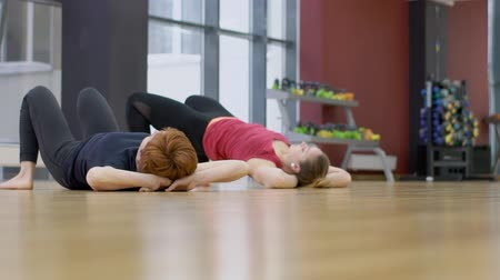 pushed : Two ladies are having a yoga class in modern gym, slow motion. Women are doing upforward bow pose on elbows near the big window and turning into other position, lying on the wooden floor on the back with knees pushed to chest.