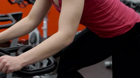 elliptical : Female athlete is on cardio training in sports club. Young woman is working on ellipsoidal machine in modern studio indoors. Fitness lady rotates pedals intensively, performing movements back and forth along elliptical trajectory. Practice affects complex