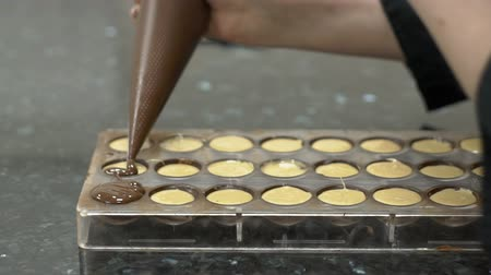 pralina : Woman covers candy with liquid chocolate from a confectionery bag. Female hands hold confectionery equipment and pour candy shape to make handmade sweets. slow motion slowmotion