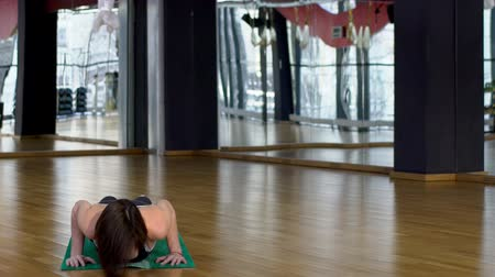 bodyweight : Attractive woman in a gym on a mate doing yoga exercises. Beautiful female figure is engaged in warm-up and performs a pose of a cobra and plank. Stock Footage