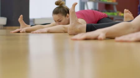 assentado : Close up of two women, who are doing stretching exercises during yoga class, slow motion. Ladies are sitting in wide-angle seated forward bend position and touching wooden floor of modern gym by their hands.