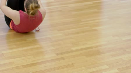 pushed : Young woman is finishing her roll oven in modern gym, slow motion. Blond lady in red top and black sport trousers is lying on the wooden floor with knees pushed to chest and starting to straighten to have the next exercise.