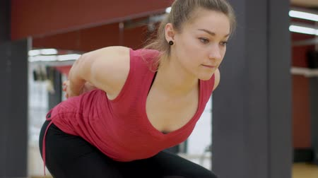 sapma : Close-up of sporty woman leaning over and flexing hands behind back. In gym female model does exercises to develop flexibility of the spine and arm muscles.