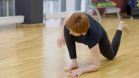 ajoelhado : Mature woman is having yoga training in modern gym, slow motion. Lady in black sportswear is standing in low lunge pose on wooden floor and stretching her leg and then turning to downforward-facing dog position.