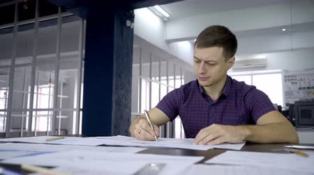 vázlat : The portrait of male architect who is streaking the blueprint looking into the results of research. The professional in t-shirt is using pen in his hand to correct the paper plans on the table in front of him. The man is working is big modern office with