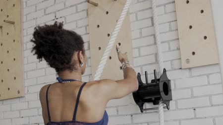 pulling up : Portrait of afroamerican woman who is pulling the rope in luxury gym. Sportswoman in blue sport top is standing in front of the white brick wall with black equipment on it and training her musucular arms with silver armlets on.
