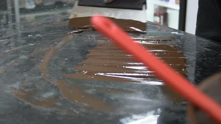 temper : Confectioner on table with a spatula conducts cooling of hot chocolate mass. Close-up of a handmade chocolate master conducts a procedure for tempering by technology and recipe. slow motion slowmotion
