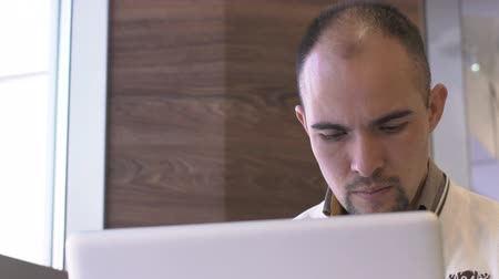 concentrando : Portrait of an unshaven bald man who works for a laptop. Close-up of a bearded mans face looks at the monitors screen carefully and seriously. slow motion slowmotion