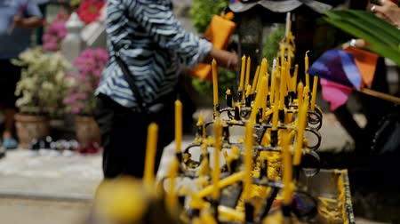 usado : Rows of yellow slim candles, which are put into black holder ouside, close up. Candlestick is metal, black and beaten. Female tourist at the background is lighting her tool to place it near the others and colourful flags are near. Vídeos