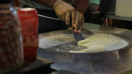 being cut up : Close up of candy rolls are being cooked in the restaurant. Male cooker is separating the slice of baked sweet paste, which had been cut before, from round steel pan by the spatula in his hand and making wraps from it. Stock Footage