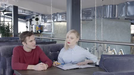 yetenekli : Female designer and male client are discussing the project in restaurant with stylish interior, slow motion. Man in red jumper and blond woman in blue shirt are sitting on velvet sofa at the wooden table with floder on and talking.