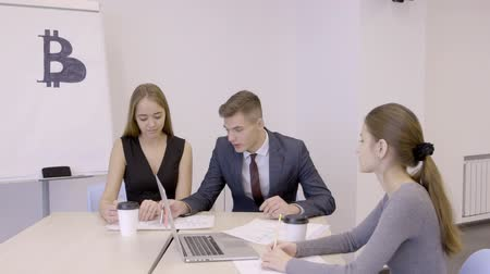 banking document : Three male and female colleagues discussing bitcoin investmens in the office, slow motion.